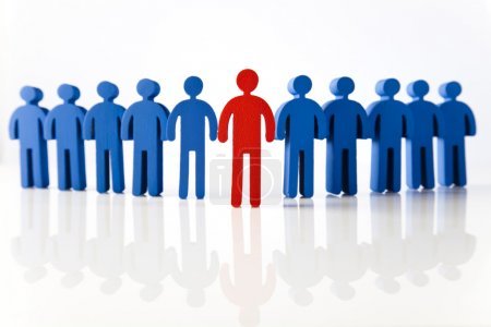 Photo for Concept of teamwork. Blue figures standing in row with one red figure in the middle - Royalty Free Image