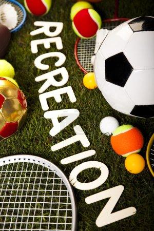 Photo pour Mot de loisirs avec des balles de sport et de l'équipement sur herbe verte - image libre de droit