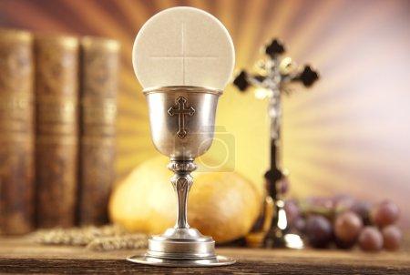 Photo pour Symbole christianisme religion. Empilement de livres de religion, pain aux graines de blé, croix et galette dans le calice - image libre de droit