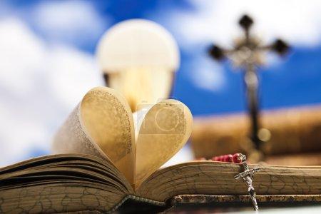 Photo pour J'adore le concept de religion. forme de coeur à partir des pages de la Bible avec du pain, des raisins et une pile de livres sur fond - image libre de droit
