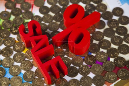 Sale sign on heap of coins