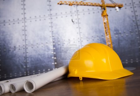 Construction plan with a crane and yellow helmet