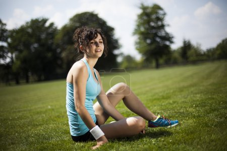 sporty woman resting on green grass