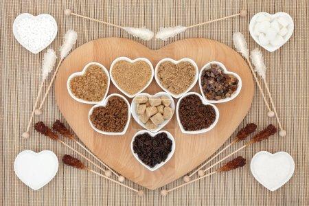 Photo pour Sélection de sucre blanc et brun dans des bols en forme de coeur avec sucettes en cristal sur fond de bambou . - image libre de droit
