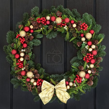 Photo for Christmas wreath with red and gold bauble decorations, bow, holly, mistletoe, pine cones and blue spruce fir over dark wood front door background. - Royalty Free Image