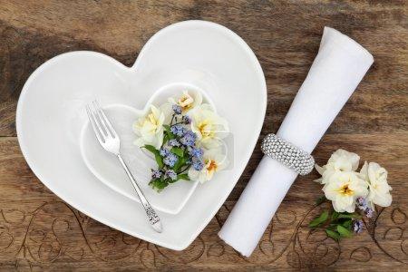 Foto de Ajuste de lugar de la tabla con corazón blanco en forma de cuencos de porcelana, antiguo tenedor plata, selección de flores de primavera y servilleta con anillo sobre fondo de roble viejo. - Imagen libre de derechos