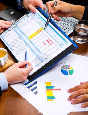 Photo pour Les gens d'affaires discutent des graphiques et des graphiques montrant les résultats de leur travail d'équipe réussi - image libre de droit