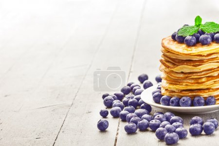 Photo for Photo of delicious pancakes with blueberries over wooden table - Royalty Free Image