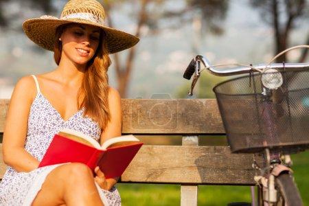 brunette femme assise sur un banc avec un livre dans ses mains
