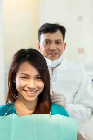 Portrait of dentist with his patient looking towards the camera