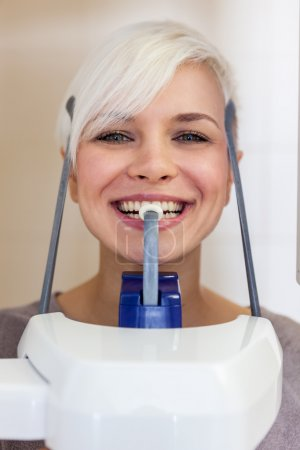 smiling blonde woman is doing a dental scan