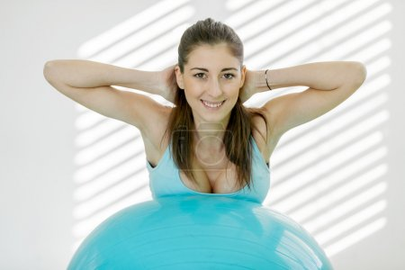 Attractive young woman is doing workout with a gym ball