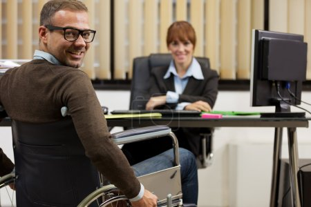 smiling man on wheelchair looking towards the camera while femal