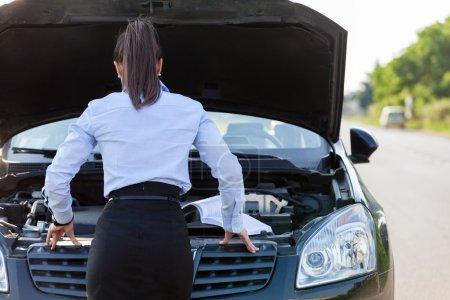 Businesswoman is looking inside the car hood