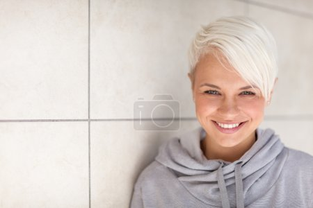 Blonde woman standing next to a wall