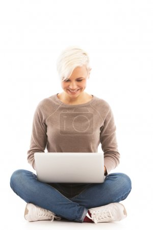 Casual dressed woman sitting on the floor with laptop over white