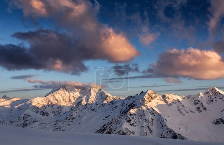 Winter snow-covered mountains at sunset. Creative toning effect. Beautiful winter landscape in Caucasus mountains