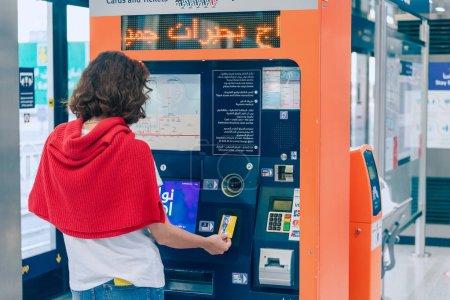 Photo pour 23 février 2021, Dubaï, EAU : une passagère réapprovisionne sa carte de transport pour un tramway ou un métro à Dubaï à l'aide d'une caisse automatique - image libre de droit
