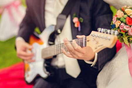 The groom plays the guitar at the wedding...