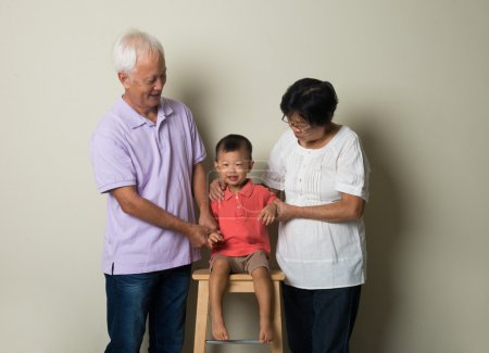 Portrait Of Chinese Grandparents With Grandson