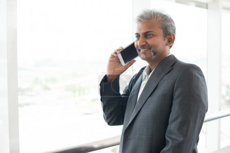 Photo for Matured indian businessman using  smartphone - Royalty Free Image