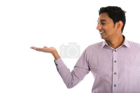 Photo for Portrait of young businessman pointing at invisible product over white background. - Royalty Free Image