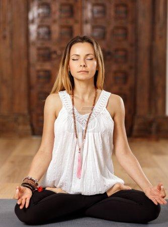Photo pour Formateur d'yoga femme attirante en posture de lotus (padmasana) - image libre de droit
