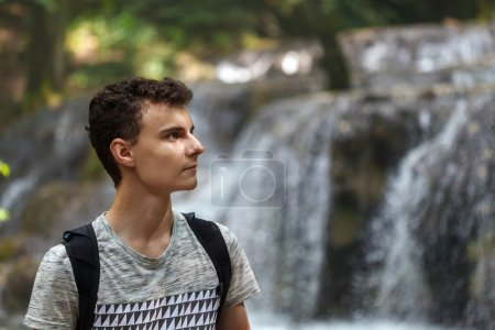 Photo for Young man hiker with backpack near a waterfall - Royalty Free Image