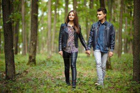 Photo pour Adolescents garçon et fille sur un rendez-vous, faire une promenade dans la forêt - image libre de droit
