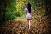 Woman walking barefoot in forest