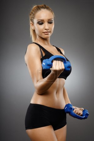 Photo for Young fit woman training with light dumbbells - Royalty Free Image