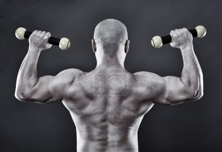 Photo for Funny image of a very strong man with light dumbbells over gray background - Royalty Free Image