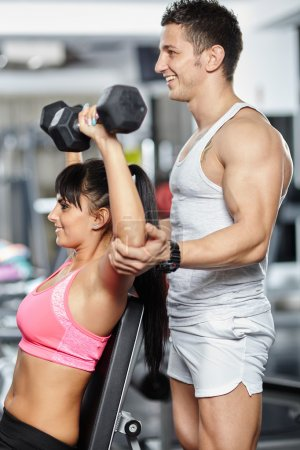 Fitness trainer helping girl in a gym