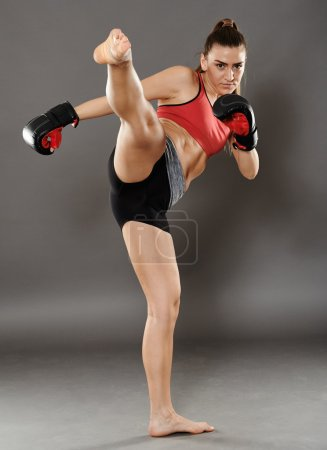 Photo for Kickbox young woman delivering a kick, over gray background - Royalty Free Image