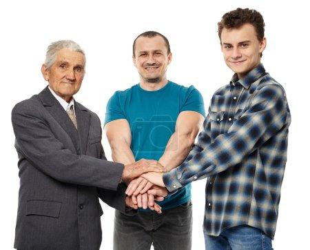 Photo pour Générations masculines - grand-père, fils et petit-fils se tenant la main, s'aidant et se soutenant mutuellement - image libre de droit