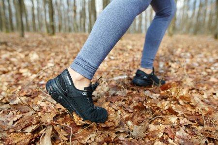 Photo pour Gros plan des jambes d'une jeune femme faisant du jogging sur un sentier dans la forêt - image libre de droit