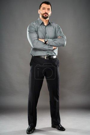 Photo pour Tout au long de l'homme d'affaires cherche bonne confiance avec bras plié posant - image libre de droit
