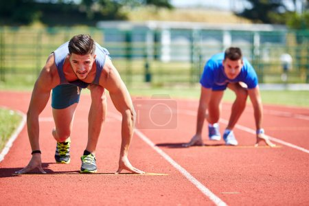 Photo for Two friends running on the lines at the stadium in a sunny day - Royalty Free Image