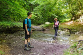Family of hikers crossing the river