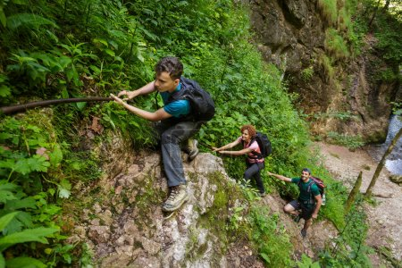 Photo pour Famille de randonneurs grimpant sur des câbles de sécurité dans un canyon - image libre de droit