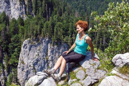 hiker sitting on the mountain peak