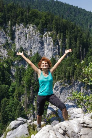 Photo for Happy woman hiker celebrating freedom on the mountain peak - Royalty Free Image