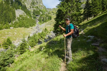 man standing on a mountain trail
