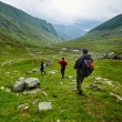Group of hikers descending on a mountain wearing r...
