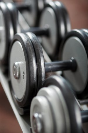 Photo for Close up of various dumbbells on the rack in the gym - Royalty Free Image