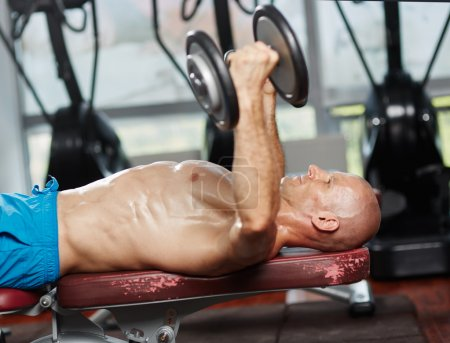 Photo for Young fit man working out at bench press with dumbbells - Royalty Free Image