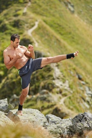 Kickboxer Shadow boxing on mountains