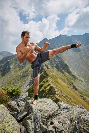 Kickboxer Shadow boxing on mountains