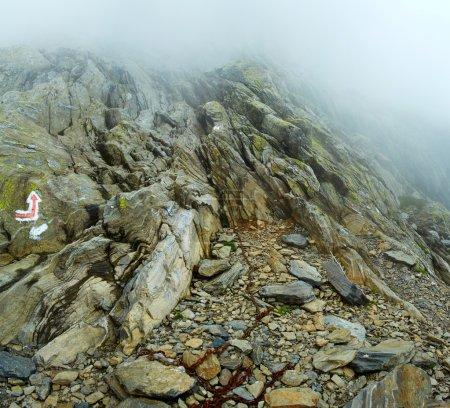 Photo pour Sentier balisé avec chaînes de sécurité à travers les montagnes rocheuses par une journée brumeuse - image libre de droit