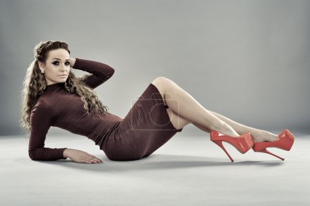 Photo for Gorgeous fashion model in tight dress and high heels posing on gray background - Royalty Free Image